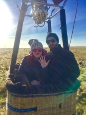 Couple standing inside balloon basket showing engagement ring
