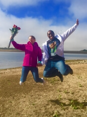 Happy couple jumping in air after hot air balloon proposal